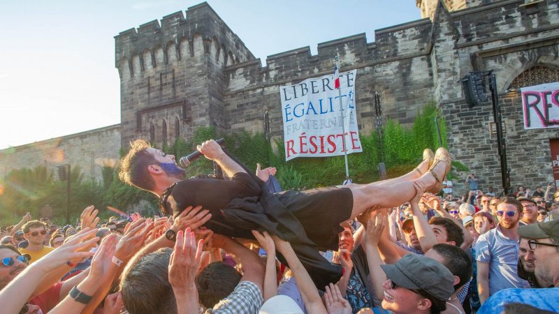John Jarboe, portraying Edith Piaf, crowd surfs off of the stage at the conclusion of the Bastille Day celebration at Eastern State Penitentiary. (Jonathan Wilson for WHYY)