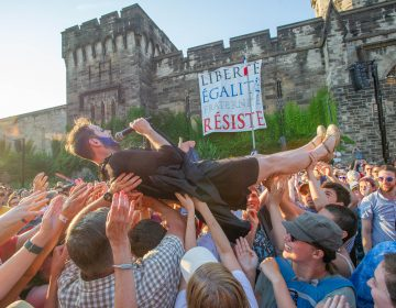 John Jarboe, portraying Edith Piaf, crowd surfs off of the stage at the conclusion of the Bastille Day celebration at Eastern State Penitentiary.