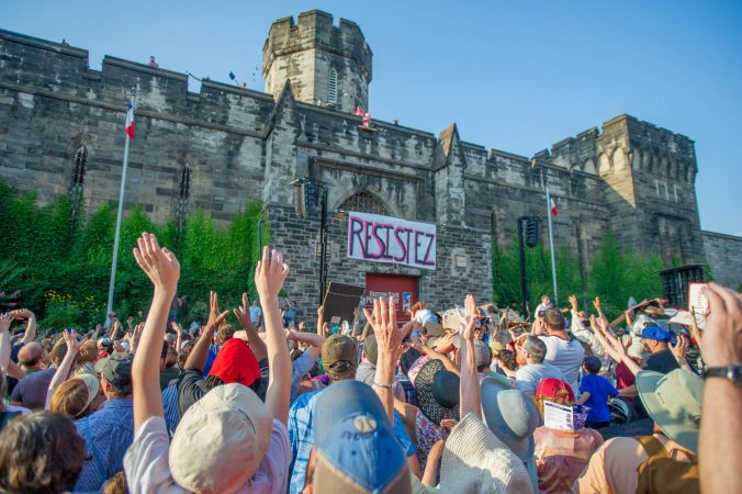 People in the crowd reach for the sky as Marie Antoinette and her minions throw Tastykakes from the top of the Eastern State Penitentiary wall.