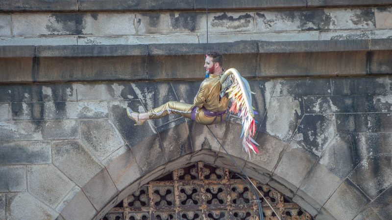 Reprising his role as Edith Piaf for the last time, John Jarboe rappels from the tower of Eastern State Penitentiary wearing a gold lame jump suit, wings, and gold heels. (Jonathan Wilson for WHYY)