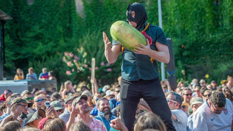 Executioner, played by Sean Kelley, psychs up the crowd before slicing watermelons with the guillotine. (Jonathan Wilson for WHYY)