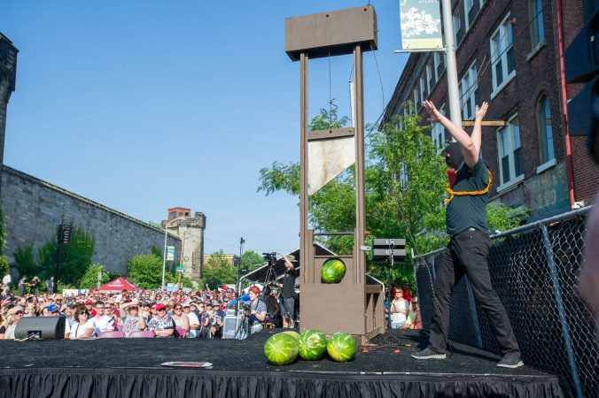 The executioner, played by Sean Kelley, releases the guillotine to slice watermelons which were then handed out to lucky members of the crowd. (Jonathan Wilson for WHYY)