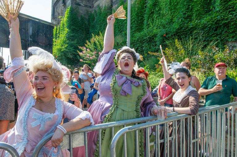 Revelers (from left) Francesca Negron, Ann Patricia, and Katherine Patterson, wear period costumes for the final Bastille Day performance on July 14, 2018. (Jonathan Wilson for WHYY)