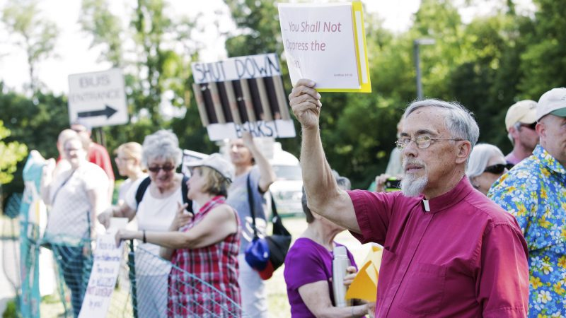 Retired Rev. David W. Brown holds a sign which reads