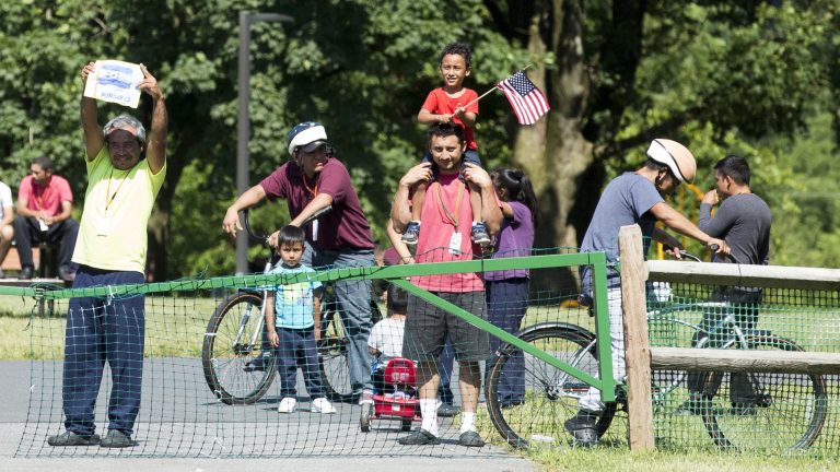 A group of immigrants detained at the Berks County Residential Center in Leesport, Pennsylvania, respond to a protest of the detention center occurring across the street from the facility on the afternoon of July 15. On the left, a man holds a handmade drawing of the Honduran flag. (Rachel Wisniewski for WHYY)