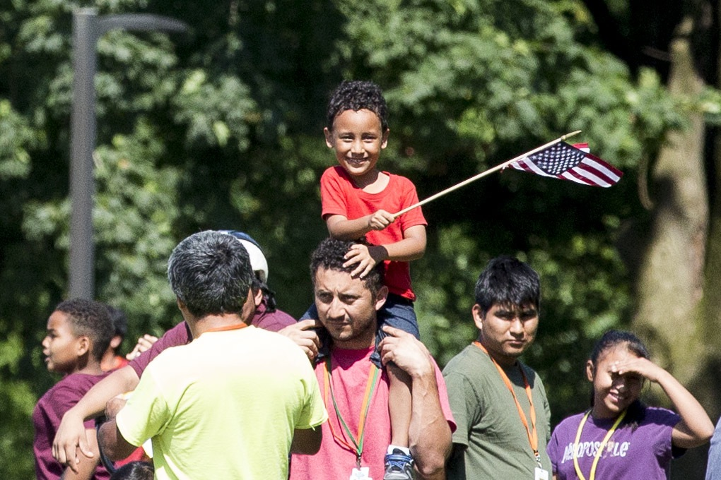 A group of immigrants detained at the Berks County Residential Center in Leesport, Pennsylvania, respond to a protest of the detention center across the street from the facility on the afternoon of July 15. At center, a young boy smiles and waves an American flag.