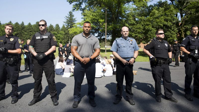 Berks County police officers form a human barricade between seated and standing protestors at the Vigil to Shut Down Berks at the Berks County Residential Center on July 15. (Rachel Wisniewski for WHYY)