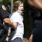 A demonstrator is arrested at the Vigil to Shut Down Berks on the afternoon of July 15. Seventeen arrests were made after group blocked a road outside the detention facility in Leesport, Pa., which is used to house immigrant families who are seeking asylum or fighting deportation. (Rachel Wisniewski for WHYY)