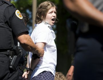 A demonstrator is arrested at the Vigil to Shut Down Berks on the afternoon of July 15. Seventeen arrests were made after group blocked a road outside the detention facility in Leesport, Pa., which is used to house immigrant families who are fighting deportation.