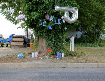Candles, balloons  and plastic flowers mark the spot where an unarmed man was shot dead by police in Vineland, New Jersey. (Emma Lee/WHYY)