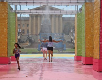 People cool off in the mister at the Eakins Oval pop-up park. (Emma Lee/WHYY)
