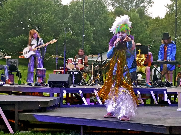 Jess Conda, as Feste, fronts the band Midsummer Madness in a glam rock version of
