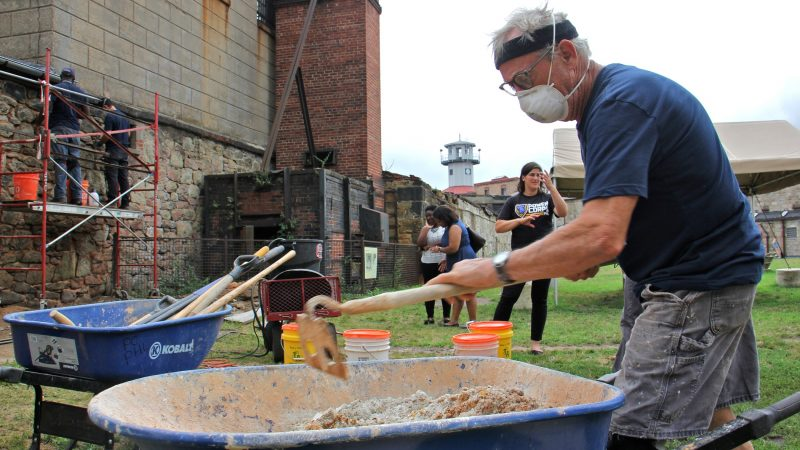 David Gibney, an independent preservationist working with the HOPE program, mixes mortar for the walls of the historic Eastern State Penitentiary. Gibney is training a new generation of preservationists. (Emma Lee/WHYY)