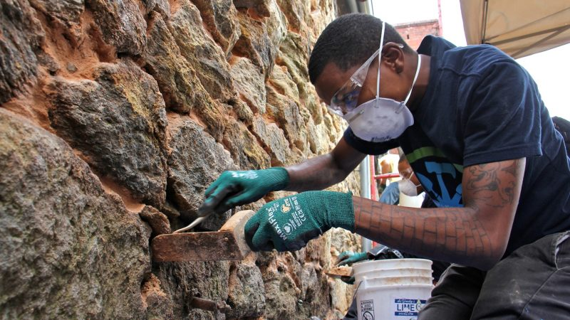 Keyana Lane, 24, (foreground) and Dyrek Davis, 20, learn the art of historic preservation while restoring the deteriorating masonry at Eastern State Penitentiary. (Emma Lee/WHYY)