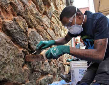 Keyana Lane, 24, (foreground) and Dyrek Davis, 20, learn the art of historic preservation while restoring the deteriorating masonry at Eastern State Penitentiary.