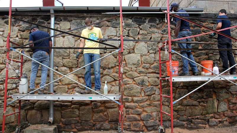 Participants in the HOPE (hands-on preservation experience) program learn a trade while helping to restore the walls of the Eastern State Penitentiary historic site in Philadelphia. (Emma Lee/WHYY)