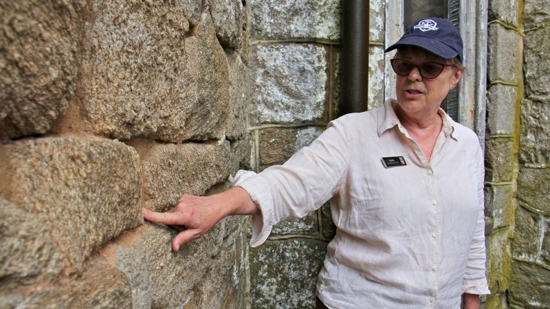 Sara Jane Elk, head of Eastern State Penitentiary Historic Site, points out deteriorating mortar in the walls of the building. (Emma Lee/WHYY)