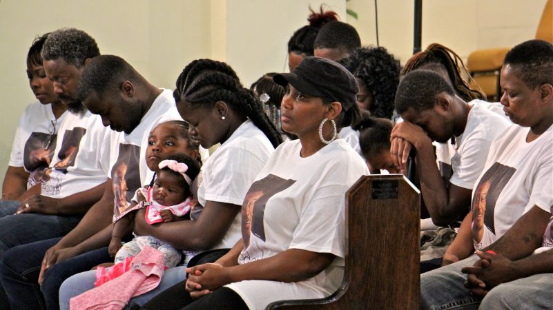 Family members of Michael White, 20, charged in the stabbing death of Sean Schellenger, 37, pray during a vigil at True Gospel Tabernacle in South Philadelphia. (Emma Lee/WHYY)