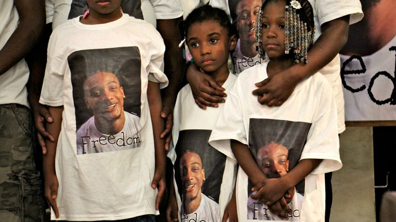 Relatives of Michael White, wearing T-shirts decorated with his photo, participate in a prayer vigil at True Gospel Tabernacle Family Church in South Philadelphia. White is charged in the stabbing death of Sean Schellenger. (Emma Lee/WHYY)