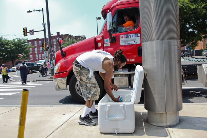 A man sells water on the median of Broad Street at Girard Avenue in the midst of a heat wave with temperatures in the mid- to upper 90s expected throughout the week. (Kimberly Paynter/WHYY)