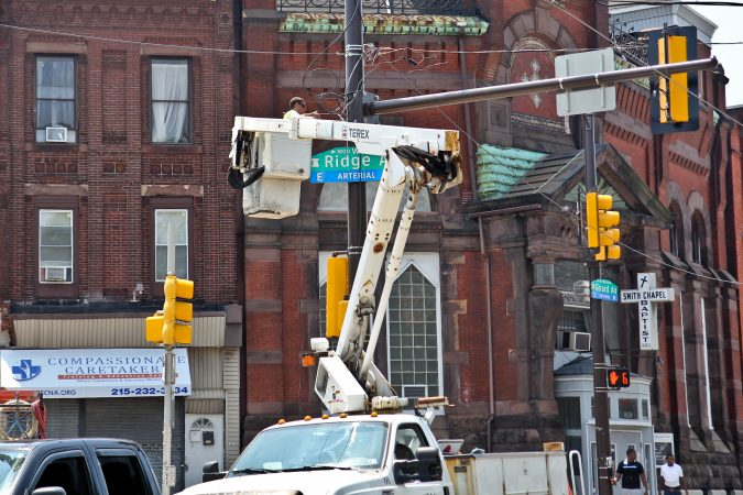 An electrician at Girard and Ridge avenues works from a crane in the midst of a heat wave with temperatures in the mid- to upper 90s expected throughout the week. (Kimberly Paynter/WHYY)