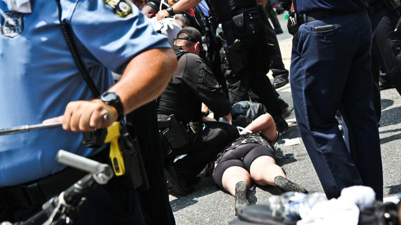 Police arrest protesters at Philadelphia's ICE office at Eighth and Cherry streets around noon Tuesday. (Kimberly Paynter/WHYY)
