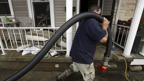A volunteer hauls a hose past flooded homes as he and others help pump water out Wednesday, July 25, 2018, in Tremont, Pa. Days of drenching rains are closing roads, sending creeks and streams over their banks and prompting some evacuations in central Pennsylvania. (Jacqueline Larma/AP Photo)