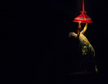Joey Arrigo, as the character Waz, performs on a lighting fixture in