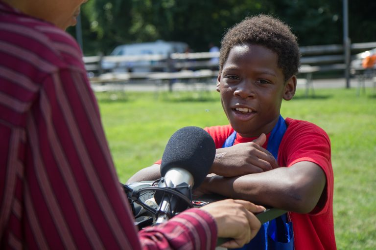 Eryn Greenwood, 10, from Eastwick, shares an experience he had with gun violence at the WURD event at Bartram's Garden. (Kimberly Paynter/WHYY)