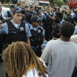 Members of the Chicago Police Department interact with an angry crowd at the scene of a police involved shooting in Chicago, on July 14. (Nuccio DiNuzzo/Chicago Tribune via AP)