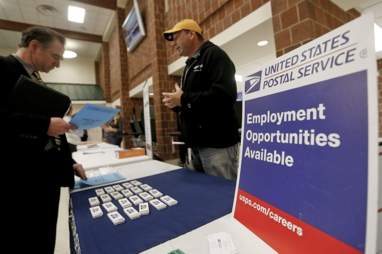 In this Thursday, Nov. 2, 2017, photo, a recruiter from the postal service, right, speaks with an attendee of a job fair in Cheswick, Pa. (AP Photo/Keith Srakocic)