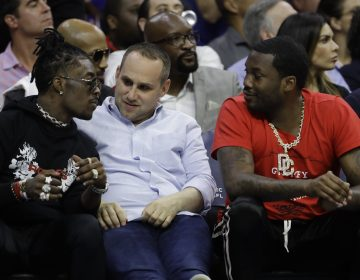 In this May 7, 2018 photo, Philadelphia 76ers' co-owner Michael Rubin, center, talks with rappers Lil Uzi Vert, left, and Meek Mill during the first half of Game 4 of an NBA basketball second-round playoff series against the Boston Celtics in Philadelphia. (AP Photo/Matt Slocum)