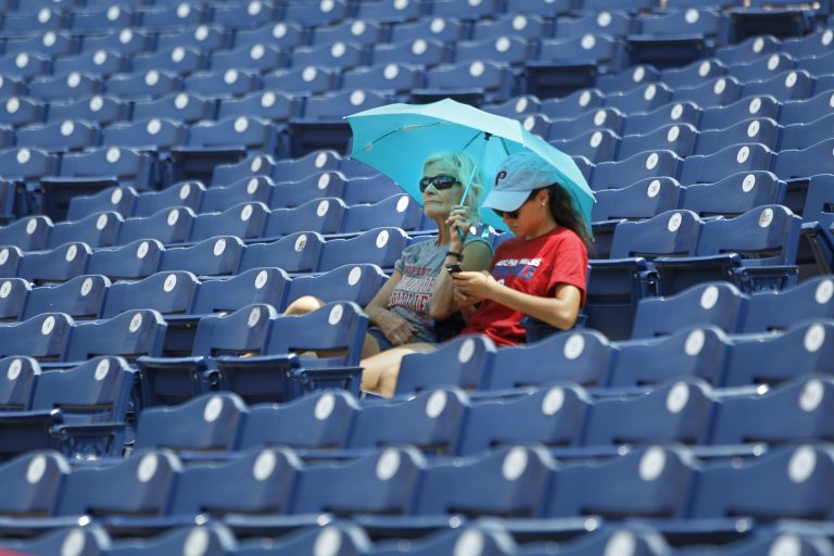 Fans find shade under an umbrella before the start of the Philadelphia Phillies versus the Washington Nationals baseball game, Sunday, July 1, 2018, in Philadelphia. (Laurence Kesterson/AP Photo)