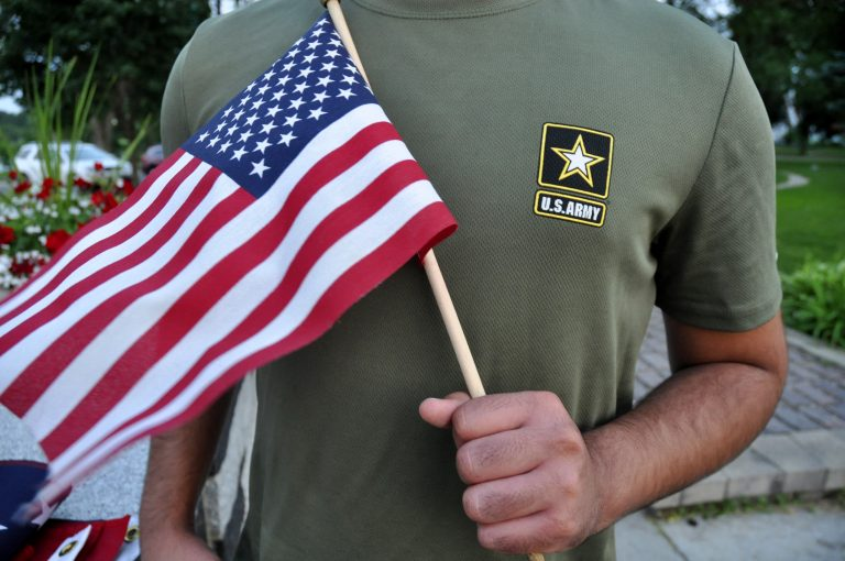 A Pakistani recruit, 22, who was recently discharged from the U.S. Army, holds an American flag as he poses for a picture. The man asked his name and location to be undisclosed for safety reasons. The AP interviewed three recruits from Brazil, Pakistan and Iran, all of whom said they were devastated by their unexpected discharges. (AP Photo/Mike Knaak)