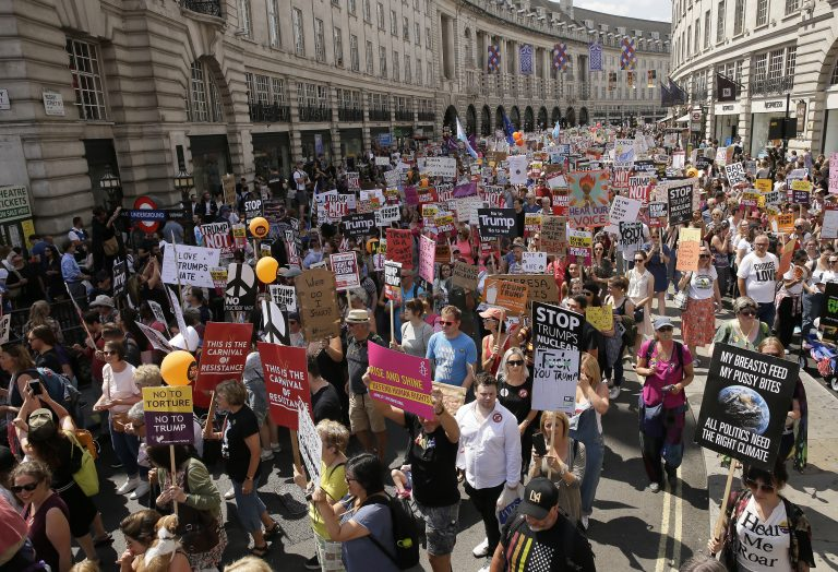 Protestors hold banners during a march opposed to the visit of U.S. President Donald Trump in London, Friday, July 13, 2018. (AP Photo/Tim Ireland)