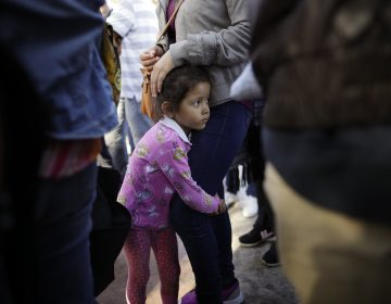 In this June 13, 2018 file photo, Nicole Hernandez, of the Mexican state of Guerrero, holds on to her mother as they wait with other families to request political asylum in the United States, across the border in Tijuana, Mexico. he separation of families at the U.S.-Mexico border caught the attention of the world and prompted mass outrage, but it only tells a small part of the story surrounding the Trump administration's immigration policy. (Gregory Bull/AP Photo, file)