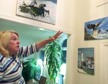 Former Department of Correction counselor Patricia May describes some of the many paintings by Delaware prison inmates that decorate her home in Hockessin, Del., Monday, July 16, 2018. May, a state corrections counselor who was taken hostage during a deadly riot at Delaware's maximum-security prison, says prison officials are to blame. (AP Photo/Randall Chase)