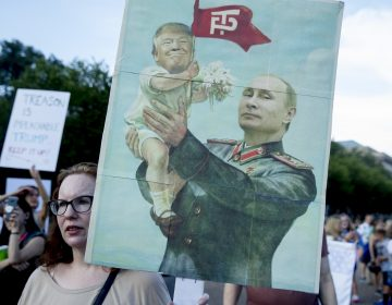 A woman holds a sign depicting Russian President Vladimir Putin and President Donald Trump during a protest outside the White House following Trump's meetings with Putin. (Andrew Harnik/AP Photo)