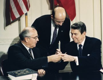 In this Dec. 8, 1987 file photo U.S. President Ronald Reagan, (right), and Soviet leader Mikhail Gorbachev exchange pens during the Intermediate Range Nuclear Forces Treaty signing ceremony in the White House East Room in Washington, D.C. Gorbachev's translator Pavel Palazhchenko stands in the middle. Pavel Palazhchenko was a constant presence as chief interpreter for Soviet leader Mikhail Gorbachev and Foreign Minister Eduard Shevardnadze, and watched from Moscow to see how the latest chapter in the US-Soviet story would unfold. (Bob Daugherty/AP Photo, File)