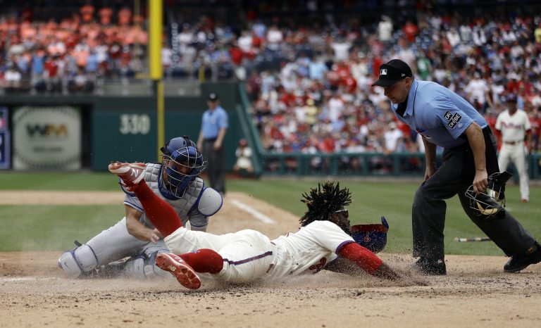 Philadelphia Phillies' Odubel Herrera, center, scores past Los Angeles Dodgers catcher Austin Barnes, left, on a three-run triple by Carlos Santana during the fifth inning of a baseball game, Wednesday, July 25, 2018, in Philadelphia. At right is umpire Adam Hamari. (AP Photo/Matt Slocum)
