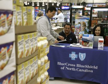 In this file photo taken Nov. 22, 2014, Blue Bridge Benefits LLC agent Patricia Sarabia, right, and Adolfo Briceno, left, with Spanish Speaking LLC, help a potential customer with Blue Cross Blue Shield at a kiosk promoting Obama Care at Compare Foods in Winston-Salem, N.C. A new poll finds that more than half of Hispanic adults have encountered a communication barrier in the health care system. (AP Photo/Gerry Broome, file)