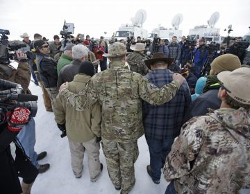 Members of the group occupying the Malheur National Wildlife Refuge headquarters hug after Ammon Bundy, center, left, one of the sons of Nevada rancher Cliven Bundy, spoke with reporters during a news conference Monday, Jan. 4, 2016, near Burns, Ore. The group calls itself Citizens for Constitutional Freedom and has sent a