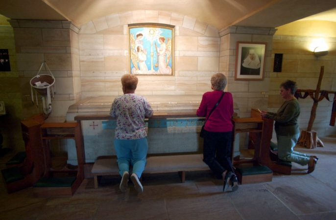 In this Oct. 2, 2000, file photo, worshippers kneel at the crypt of Saint Katharine Drexel at her national shrine on the Sisters of the Blessed Sacrament's suburban Philadelphia estate in Bensalem, Pa. (AP Photo/Dan Loh, File)