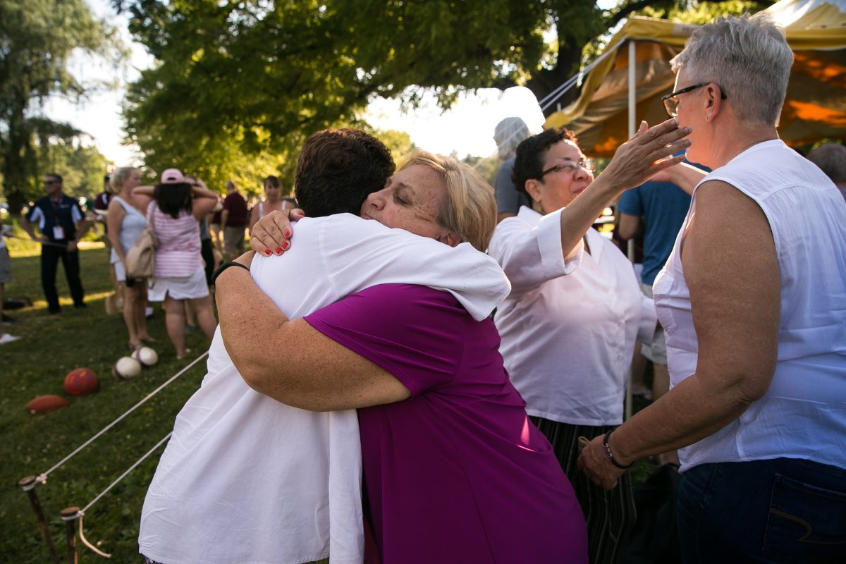 Alumni Linda Riley, left, receives a hug from Cheryl Gillick, center, as Lee Ann Riley, second from right, receives a hug from Laura Masker, far right, at a Cadets alumnipicnic Saturday. The twins have both accused Hopkins of abuse.