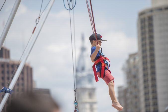 At Logan Circle, Eric Li takes his turn at bungee jumping at the Party on the Parkway. (Jonathan Wilson for WHYY)