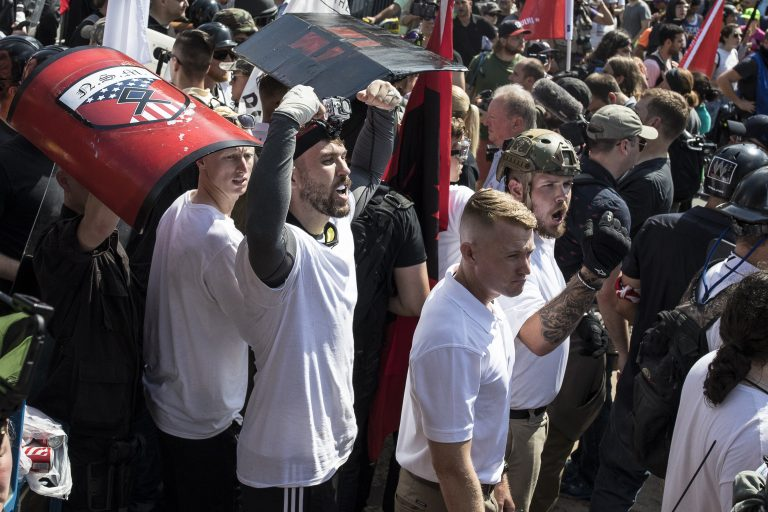 Michael Miselis, standing in the crowd with both arms raised, was front and center during the violence in Charlottesville last summer. Miselis holds a national security clearance for his work with defense contractor Northrop Grumman. (Edu Bayer, special to ProPublica)