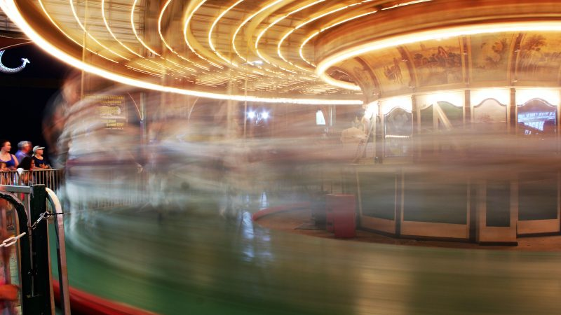 The riders blur by as they reach for the ring on the carousel at Gillian's Wonderland Pier in Ocean City. (Bill Barlow/for WHYY)