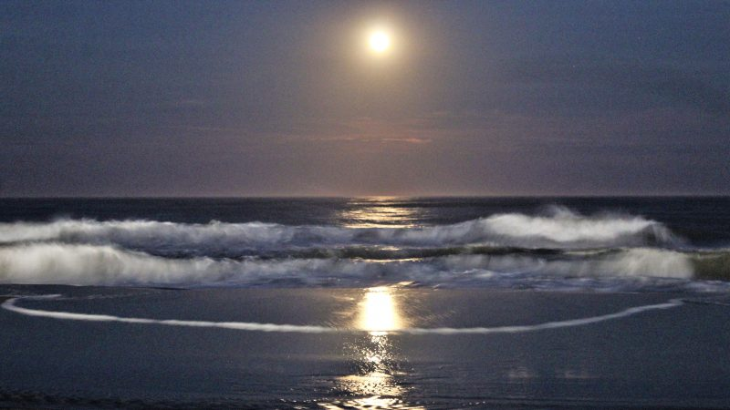 Not far from the bustle and noise of the Boardwalk, the view over the ocean is calm and quiet as the waves reflect the moon. (Bill Barlow/for WHYY)
