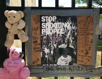Stuffed animals and a sign at the Tyree Bates memorial. (Peter Tobia/for WHYY)