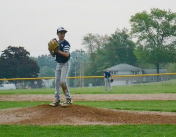 Twelve-year-old Jarryn Myers prepares to pitch. Two years ago, Myers lost his father to a heroin overdose. Jarryn helped police to find the man who sold his dad the fatal dose. (Brett Sholtis/Transforming Health)